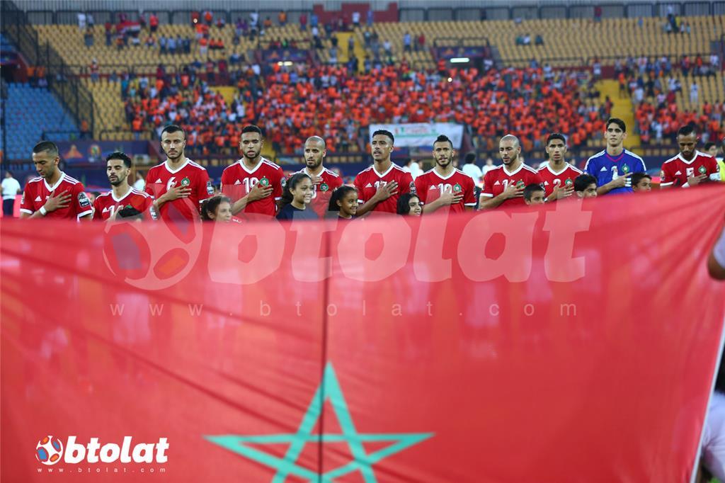 علم المغرب ومن خلفه لاعبي المنتخب